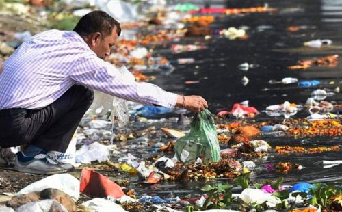 A-man-throws-the-puja-offerings-in-Yamuna-River-at-the-end-of-Navratri-festival-in-New-Delhi