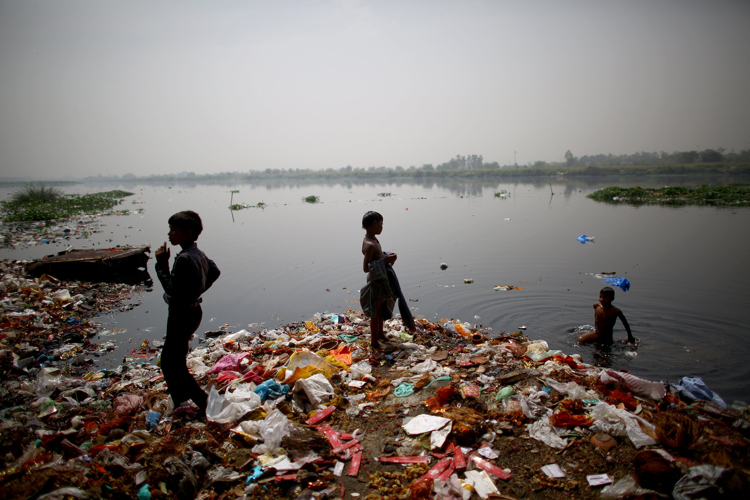 Children who live along the banks of the Yamuna River in ramshackle huts hunt for coins and anything valuable they can collect