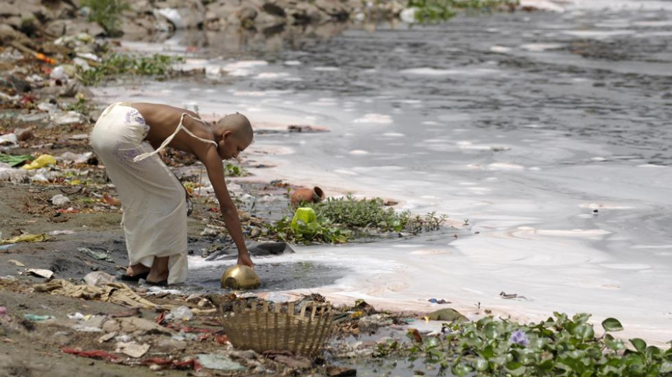 man fills water from the polluted river Yamuna in New Delhi